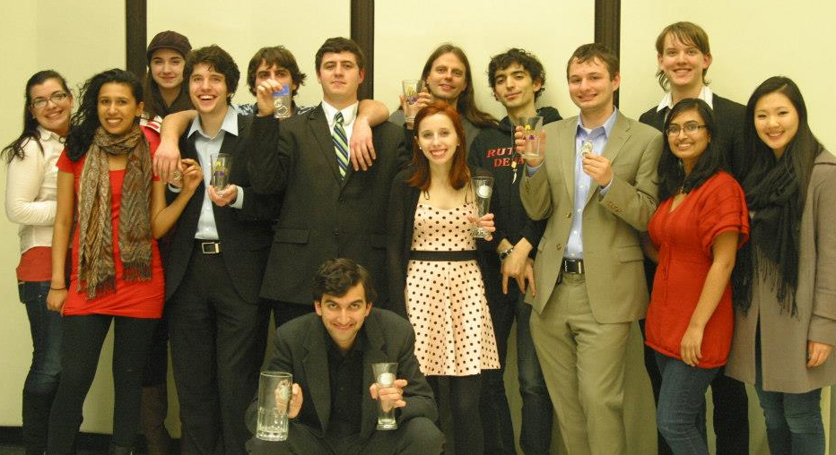 The jubilant crowd of Rutgers debaters after the announcement of Rutgers winning their second tournament this season.  Debaters are displaying their Albany-themed glasses that were given as awards.  Left to right:  Gabi Cozzolino, Deepta Janardhan, Raynee Morris, Henry Phipps, Kyle Bomeisl, Adam Bomeisl, Quinn Maingi, Alex Jubb, Storey Clayton, Arbi Llaveshi, Russell Potter, Jason Boyle, Nisha Kumar, and Rachel Moon